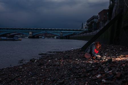 beachcombing: A young woman is beachcombing on the banks of the Thames in London at night Stock Photo