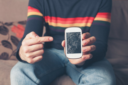 A young man is sitting on a sofa and is pointing at a broken smart phone with a cracked screen