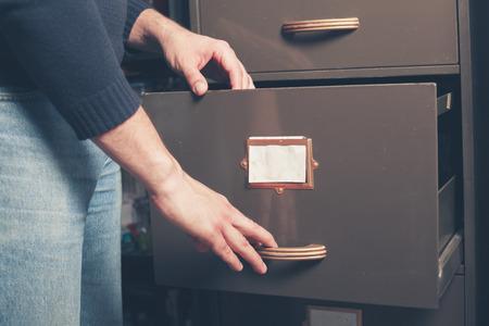 file cabinet: Un joven se est� abriendo un archivador