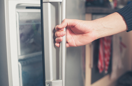 refrigerator: The hand of a young man is opening a freezer door