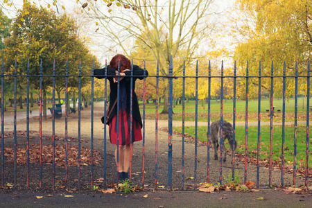 depressed woman: A sad woman is standing by afence in the park with a dog