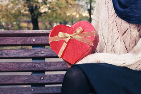 A young woman is sitting on a park bench with a heart shaped box photo