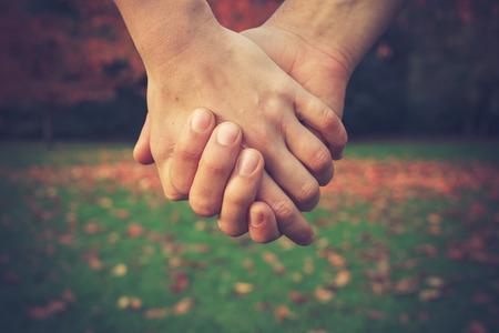 Ciérrese para arriba en un par de la mano en el parque en otoño Foto de archivo - 33797316