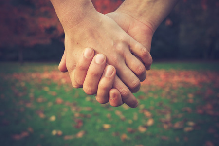 Close up on a couple holding hands in the park in autumn Standard-Bild