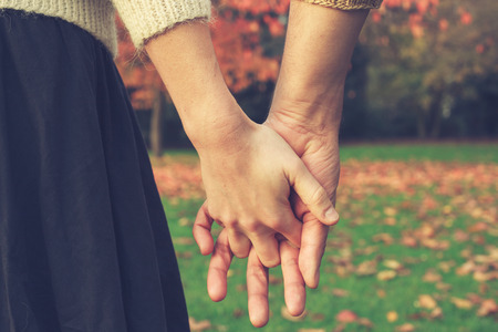 Close up on a couple holding hands in the park in autumn Archivio Fotografico