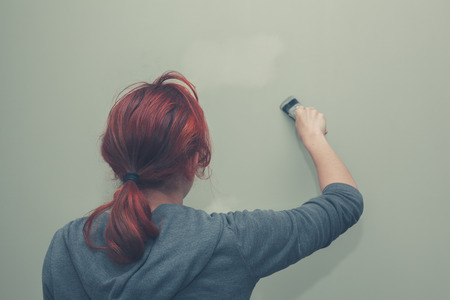 patching: A young woman is painting and patching up a green wall