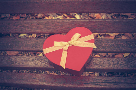 A red heart shaped box on a park bench in autumn photo