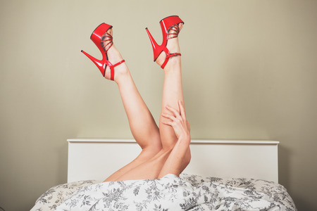 feet naked: A woman is lying in bed wearing red high heeled shoes and is raising her legs Stock Photo