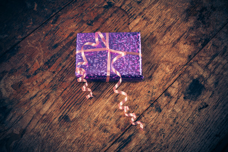 gift wrapped: A gift wrapped present on a wooden table