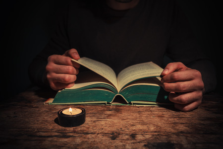 A man is reading a big book by candle light at night photo