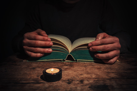 study table: A man is reading a big book by candle light at night Stock Photo