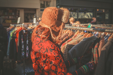 street market: A woman wearing a winter hat is browsing jackets on a rail at a street market