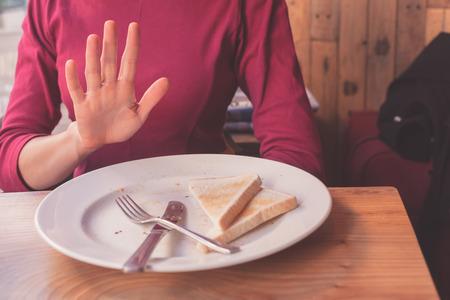 Una mujer en una dieta libre de gluten está diciendo no gracias a la tostada Foto de archivo - 34659140