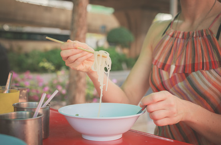 eating noodles: A woman is sitting at a table in the street and is eating noodles