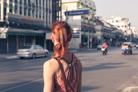 exotic woman: A young caucasian woman is walking on the street in an Asian country