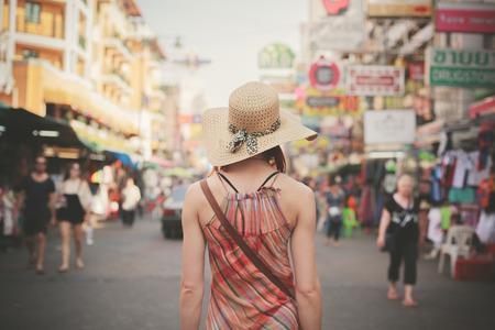 Bakifrån av en ung kvinna gående den berömda backpacker gatan Khao San i Bangkok, Thailand