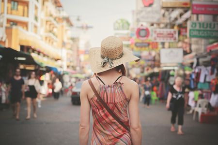 backpackers: Rear view of a young woman walking the famous backpacker street Khao San in Bangkok, Thailand