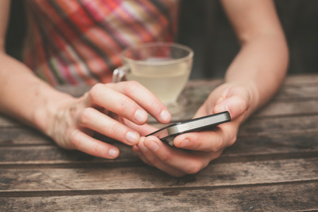 A young woman is drinking tea and using her smart phone at a wooden table