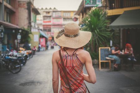 city alley: A young woman is walking on the street of an asian country on a sunny day