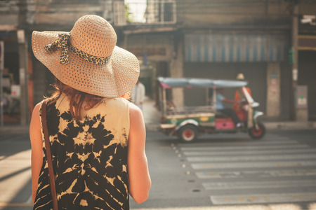 A young woman wearing a hat is walking in the streets of an asian country