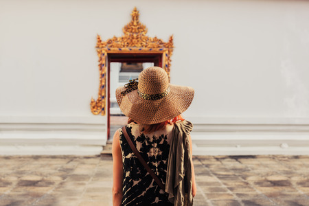 future buddha: A young woman is looking at the elaborate entrance to a buddhist temple