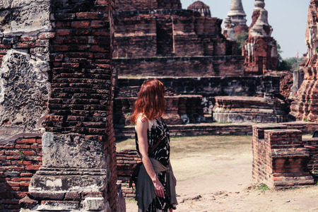 A young woman is exploring the ancient ruins of a buddhist temple city photo
