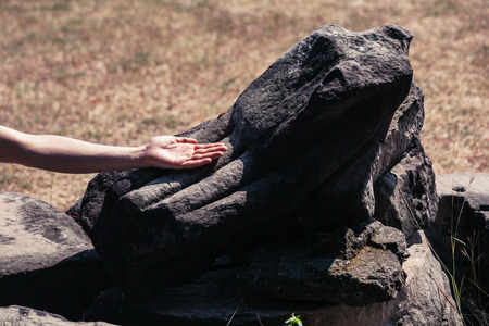 The hand of a woman is touching the hand of an ancient statue photo
