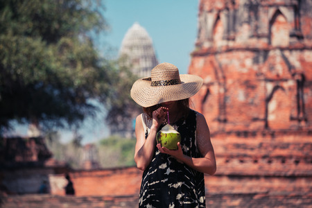 A young woman is drinking juice from a coconut near the ruins of an ancient buddhist temple photo