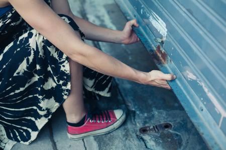 Une femme déverrouille et ouvre une porte de garage