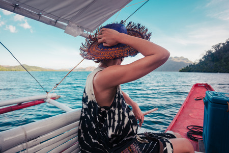 adult cruise: A young woman wearing a hat is on a boat in the tropics