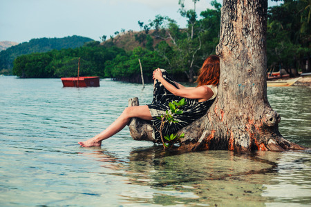 sitting up: A young woman is sitting up against a tree in the water on a tropical beach
