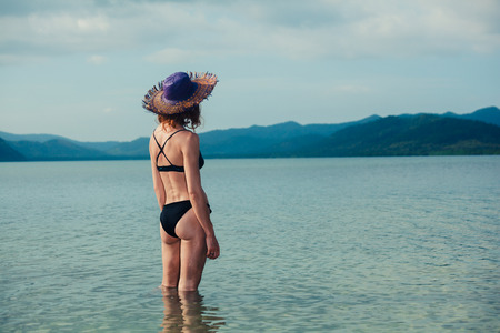 bikini island: A young woman wearing a bikini is standing in the water and is looking at a tropical island Stock Photo