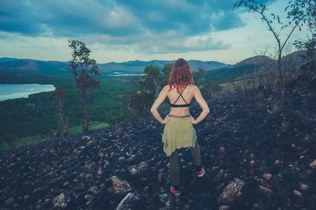 clima tropical: Una mujer joven est� de pie en una colina quemada por un incendio forestal en un clima tropical Foto de archivo