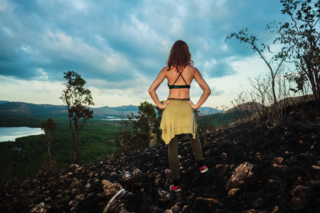 wild fire: A young woman is standing on a hill scorched by a wild fire in a tropical climate