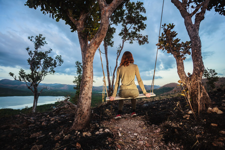 wild fire: A young woman is sitting on a swing on a hill burned by a wild fire Stock Photo