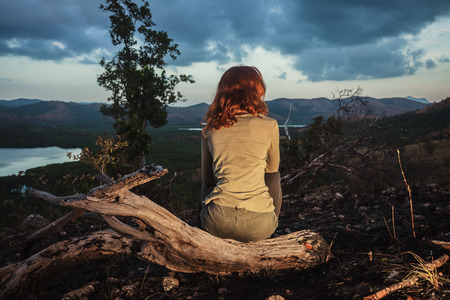 wild fire: A young woman is sitting on a hill burned by a wild fire
