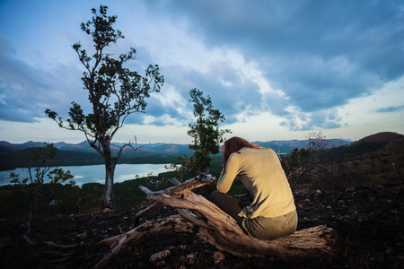 wild fire: A sad young woman is sitting on a hill burned by a wild fire Stock Photo