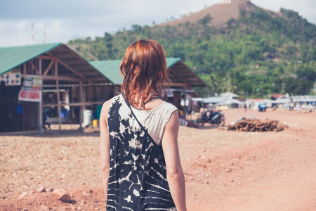 developing country: A young caucasian woman is walking around a small town in a developing country