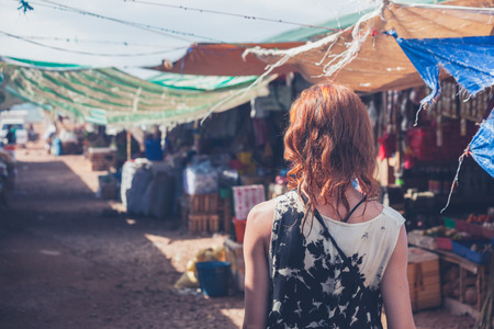 coron: A young caucasian woman is walking around a small town in a developing country