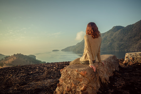 daybreak: A young woman is sitting on an unusual rock on a mountain overlooking a bay at sunrise in a tropical climate