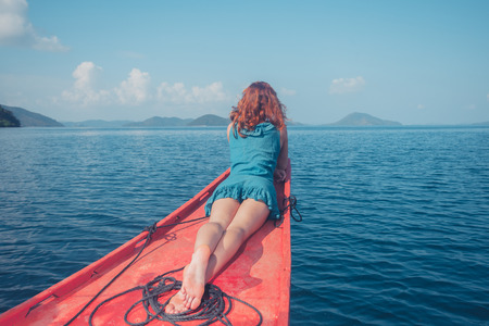 adult cruise: A young woman is relaxing on the bow of a small boat in a tropical climate