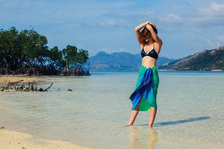 A slim young woman wearing a colorful sarong is standing on a tropical beach