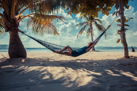 rest and relaxation: A young woman is relaxing in a hammock on a tropical beach Stock Photo