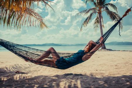젊은 여자가 열대 해변에 그물 침대에서 휴식
