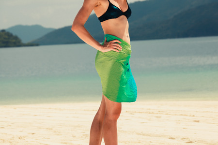 sarong: A young woman wearing a colorful sarong is standing on a tropical beach