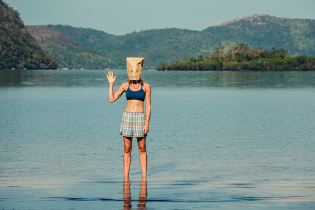 paper bag: A silly young woman wearing a paper bag over her head is standing on a tropical beach and is waving