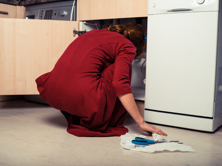 A young woman is trysing to fix the plumbing under the kitchen sink photo