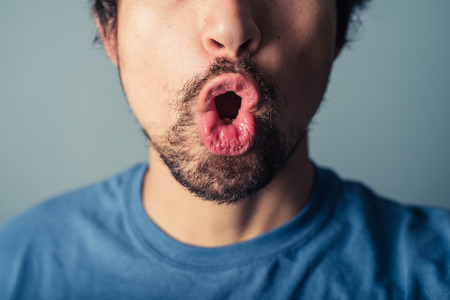pulling faces: A young man with a beard is pulling silly faces Stock Photo