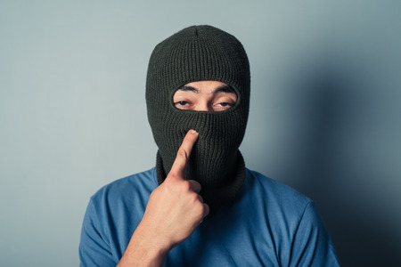 nose picking: A stupid man wearing a balaclava is trying to pick his nose