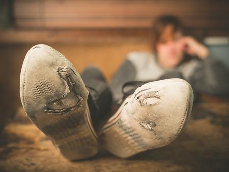 Een jonge vrouw, gekleed in versleten schoenen rust haar voeten op een tafel thuis